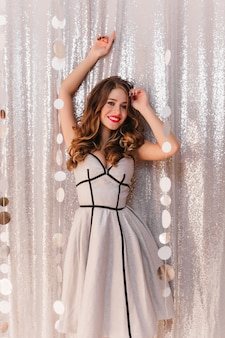 Full-length photo of young woman in lush silver dress with black stripes. lady with wavy hair and red lips on brilliant wall.