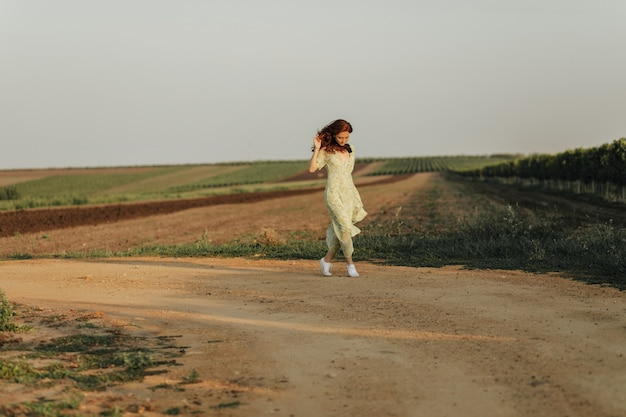 Full length photo of young woman with ginger wavy hair in long stylish green and yellow dress and light sneakers posing wall of field
