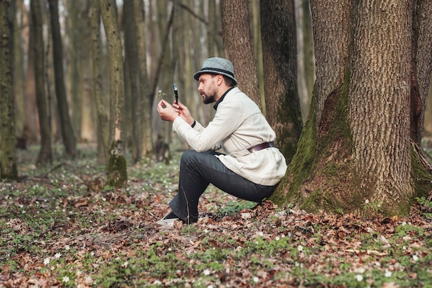 Full-length pic of well-dressed man looking at flower through magnifier sitting against tree