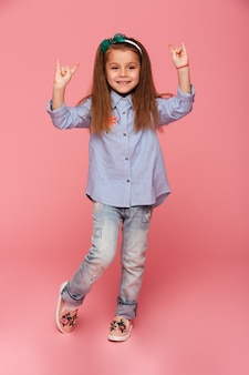 Full-length picture of funny little girl gesturing rock sign with two hands