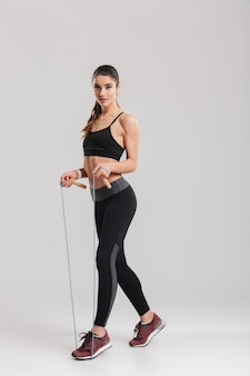 Full-length picture of gorgeous woman in gym looking  and jumping rope, isolated over gray wall