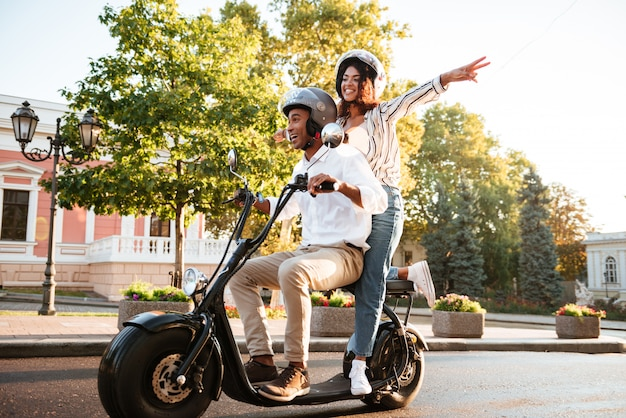 Full length picture of happy african couple rides on modern motorbike on the street