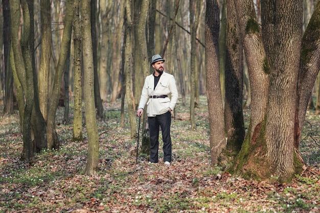 Беззаботный элегантный мужчина в полный рост, опираясь на палку, стоит среди стволов деревьев