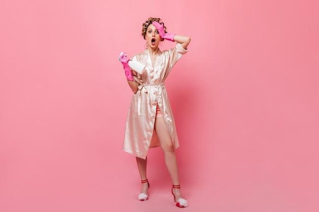 실크 가운과 분홍색 고무 장갑을 입은 여성의 전신 사진