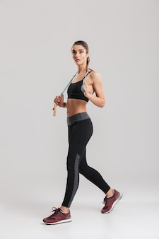 Full-length picture of slim woman looking aside and holding skipping rope on her neck, isolated over gray wall