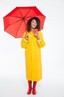 Full length picture of smiling african woman in raincoat