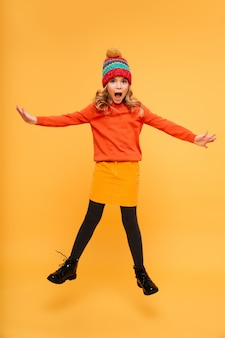 Full length playful shocked young girl in sweater and hat jumping and looking at the camera over orange