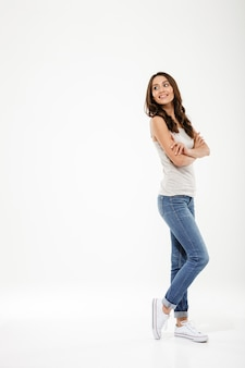 Full length pleased brunette woman posing sideways with crossed arms looking back over gray