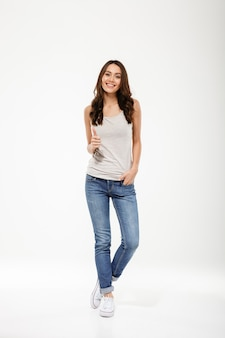 Full length pleased brunette woman with arm in pocket showing thumb up and looking at the camera over gray