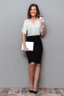 Integrale della donna piacevole in vestiti di affari con il computer della compressa e la tazza di caffè in mani che esaminano la macchina fotografica