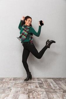 Портрет красивой африканской женщины в шарфе в полный рост, прыжки с мобильным телефоном в руке
