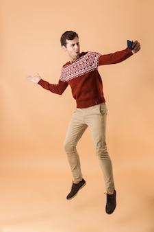 Портрет в полный рост красивый молодой человек прыгает