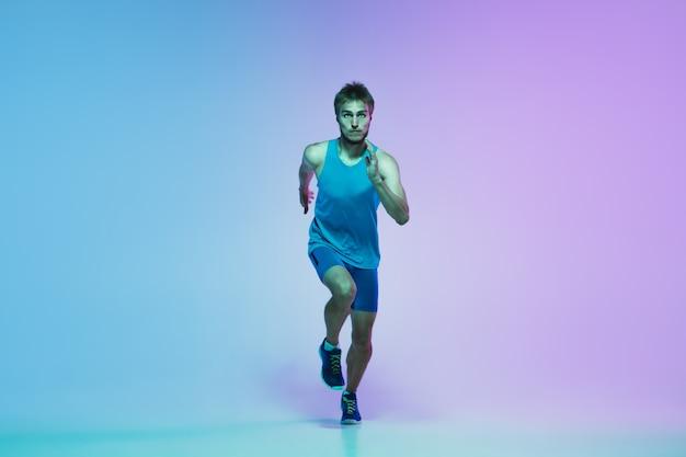 Full length portrait of active young caucasian running, jogging man on gradient studio in neon light