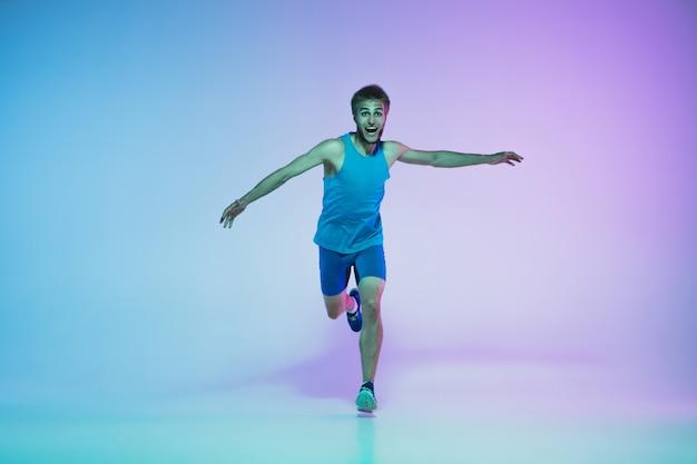Ritratto integrale di giovane attivo caucasico in esecuzione, jogging uomo su studio sfumato alla luce al neon