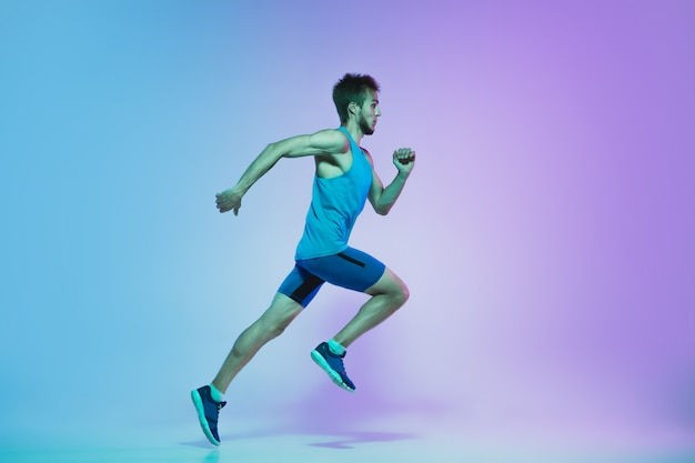 Full length portrait of active young caucasian running, jogging man on gradient studio in neon light