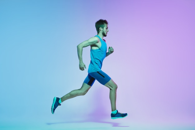 Full length portrait of active young caucasian running, jogging man on neon wall