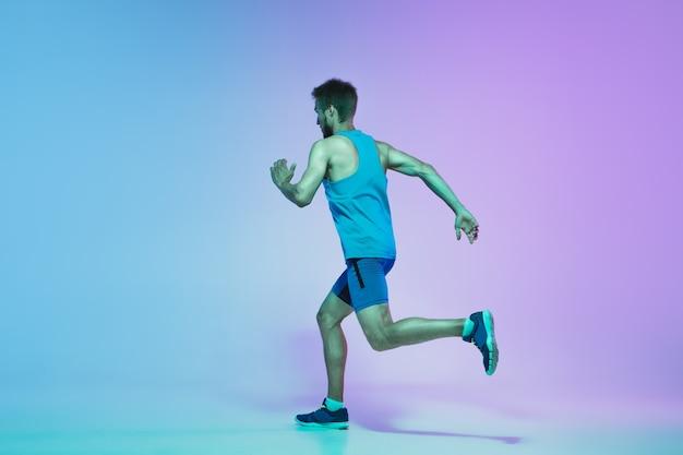 Ritratto a figura intera di giovane caucasico attivo che corre, fa jogging in neon