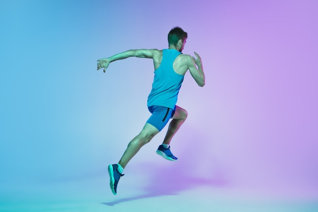 Full length portrait of active young caucasian running, jogging man