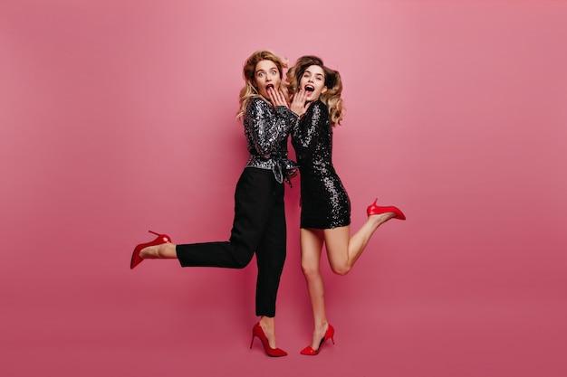 Ritratto integrale della ragazza adorabile in scarpe rosse che scherza intorno con l'amico. sorelle caucasiche meravigliose in posa prima della festa.