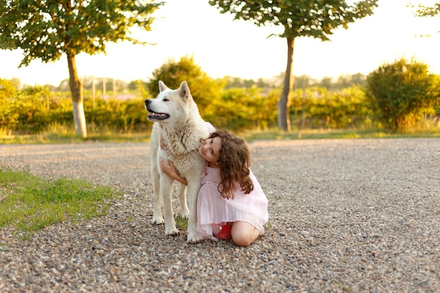 Full length portrait of an adorable little girl hugs her big dog spending time together outside in the summer. space for text.