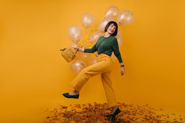 Ritratto integrale di donna adorabile che balla con palloncini festa. tiro al coperto di beata ragazza bruna in pantaloni gialli divertendosi nel suo compleanno.
