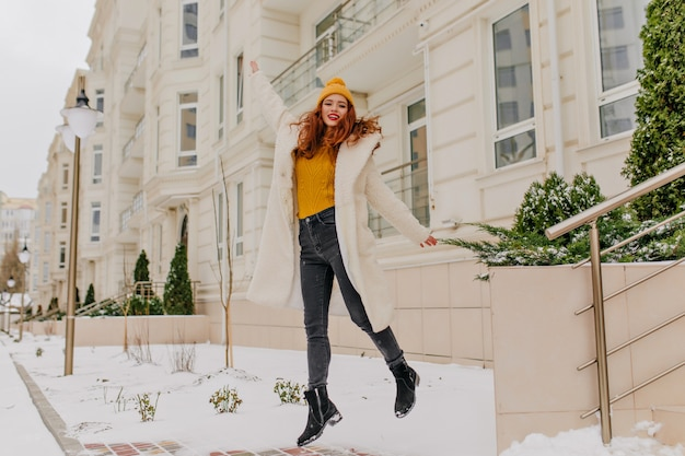 Full-length portrait of adorable woman with ginger hair dancing at the yard. amazing girl fooling around in winter.