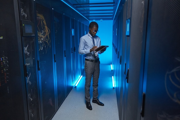 Full length portrait of african american man standing by server cabinet while working with supercomputer in data center and holding tablet, copy space
