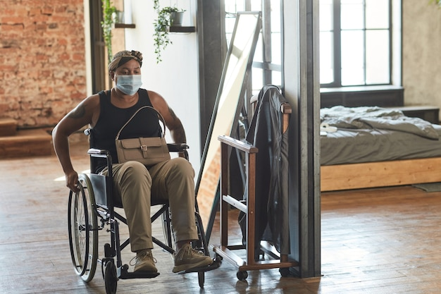 Full length portrait of african-american woman in wheelchair wearing mask ready to go out, copy space