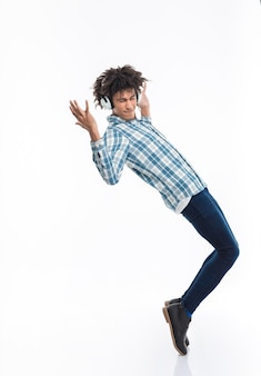 Full length portrait of afro american man with headphones dancing isolated on a white wall