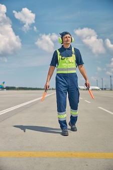 Full-length portrait of an aircraft marshaller with a pair of wands staring into the distance