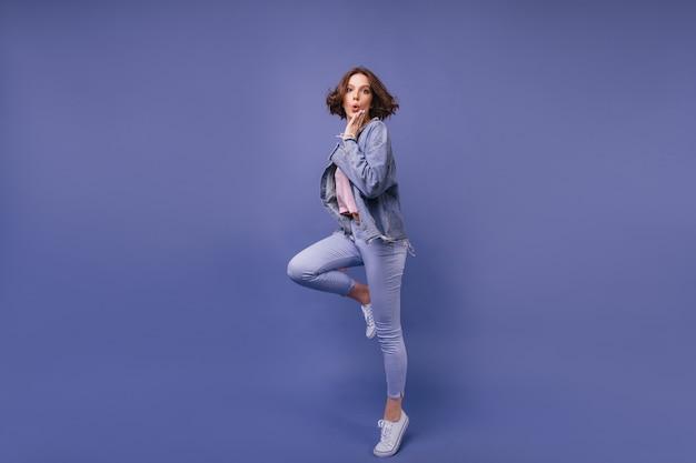 Ritratto integrale di bella signora stupita in jeans. ragazza curiosa riccia che salta.