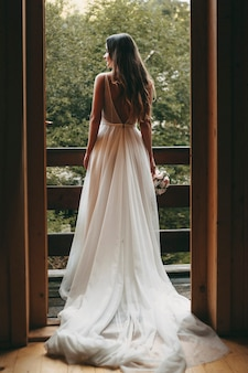 Full length portrait of a amazing bride looking outside on the balcony waiting her groom.