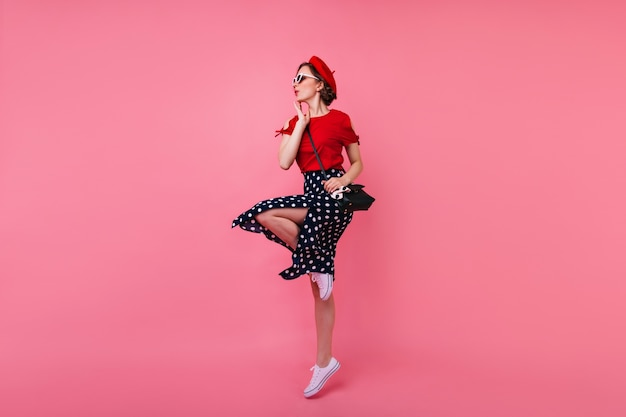 Full-length portrait of appealing slim girl. wonderful female model in beret and skirt dancing.