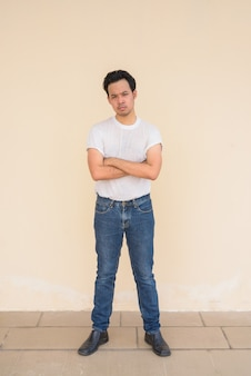 Full length portrait of asian man wearing white t-shirt against plain background outdoors