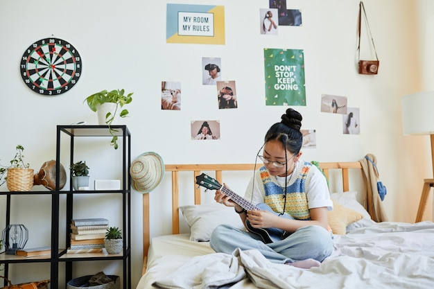 Full length portrait of asian teenage girl playing ukulele while sitting on bed in cozy room, copy space