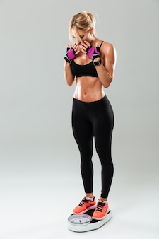 Full length portrait of a athlete woman standing on weights