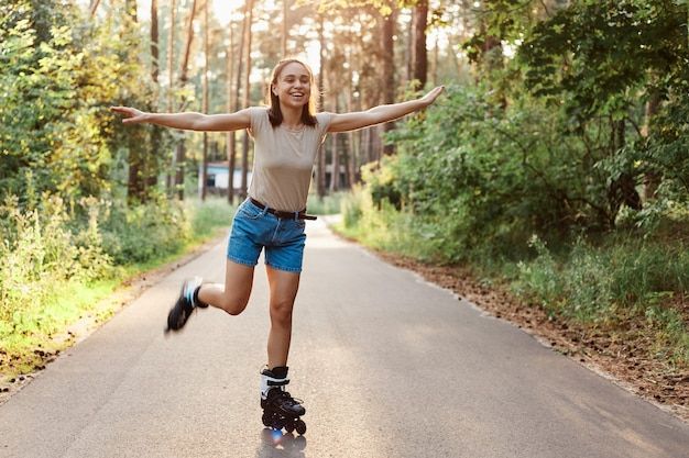 Full length portrait of attractive slim woman wearing casual style attire riding roller skates, pretending she is flying, raised arms, looking away with toothy smile.