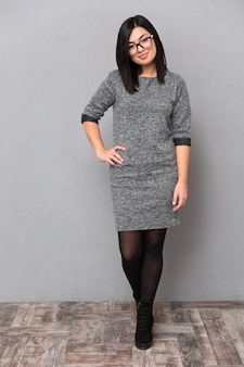 Full length portrait of attractive woman in dress and glasses standing on gray wall