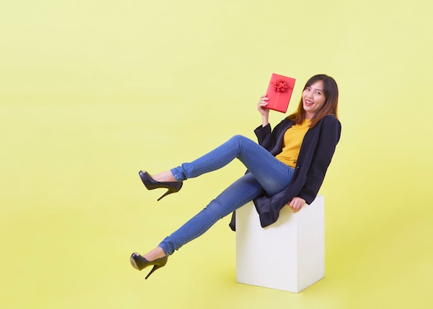 Портрет в полный рост привлекательная молодая женщина, держащая подарок, сидя на белом кубе, изолированном желтом фоне
