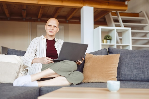 Full length portrait of bald adult woman working from home and looking at camera while sitting on comfy couch in modern home interior, alopecia and cancer awareness, copy space