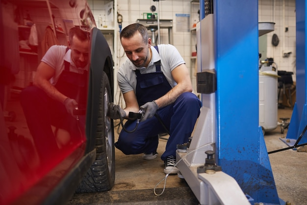 Full length portrait of bearded car mechanic checking pressure in tires during vehicle inspection in garage shop, copy space