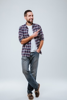 Full length portrait of bearded man in shirt pointing away