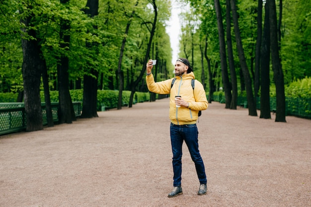 Full length portrait of bearded young man dressed in yellow jacket, jeans and black cap having walk across green park