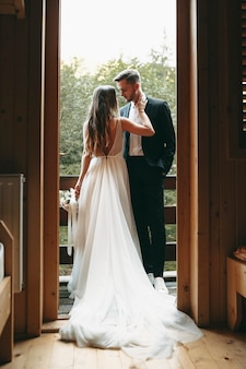 Full length portrait of a beautiful bride and groom embracing on the balcony before wedding looking to each other.