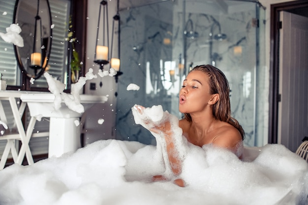 Full length portrait of beautiful brunette woman blowing foam while taking relaxing bath
