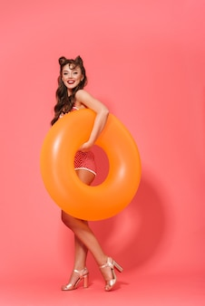 Full length portrait of a beautiful cheerful pin-up woman wearing swimsuit standing isolated
