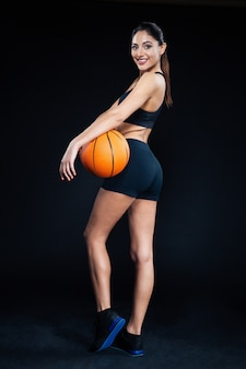 Full length portrait of a beautiful fitness woman holding basketball ball and looking back at camera on black background