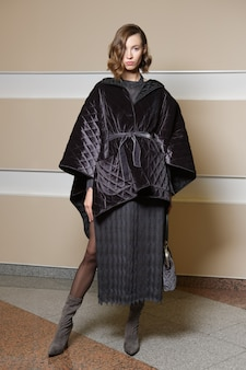 Full length portrait of beautiful girl in knitted dress and poncho coat.