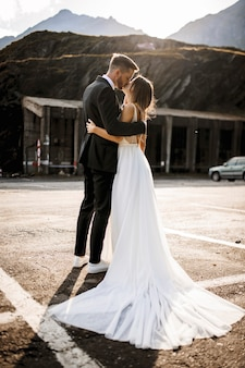 Full length portrait of a beautiful romantic wedding couple embracing and kissing against sunserise.