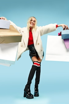 Ritratto integrale di bella donna bionda divertente sorridente che cammina con i sacchetti della spesa variopinti isolati sopra il fondo blu dello studio. lo stile di vita, la moda, la vendita, il concetto shopaholic